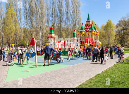 Children play on the playground at the spring park in sunny day - Stock Photo