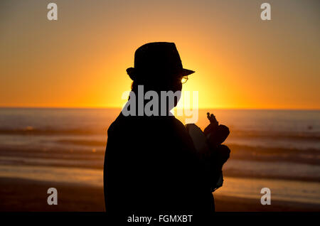 a man plays guitar on the beach at sunset, La Jolla, California, USA - Stock Photo