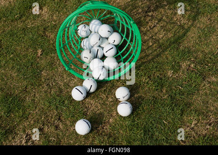 Balls tumbled from basket on driving range of golf club. - Stock Photo