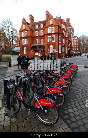 Santander Cycles hire bicycles at a docking station in Exhibition Road, Kensington, London, England - Stock Photo