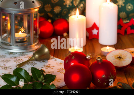 Christmas decoration with firing candles and lanter, red christmas balls with stars and bell - Stock Photo