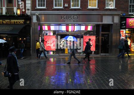 People walking past Kiko Milano cosmetics store on a rainy January evening, near Covent Garden, London, England - Stock Photo