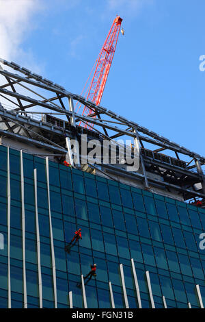 Workers on glass facade of building on Victoria Circle construction site, Victoria, London, England UK - Stock Photo
