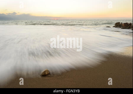 Ocean Sunset is an ocean rock on a sandy beach with a gentle wave rolling in and a soft pastel sunset on the horizon. - Stock Photo