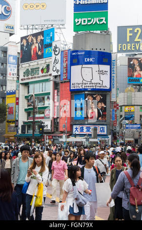 Tokyo Japan crowds rush moving walking in the busy Shibuya Station area of Shilbuya Crossing with locals rushing - Stock Photo