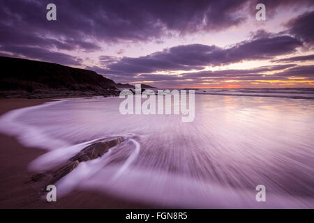 Sunset at Welcombe Mouth Beach in North Devon, UK. A wave is rushing over the pristine sand and rocks with view - Stock Photo