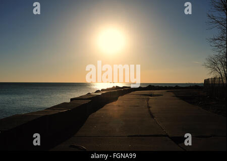 The sun rises above Lake Michigan and a stretch of a walkway along the lake on Chicago's South Side. Chicago, Illinois, - Stock Photo