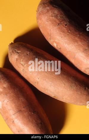 Three sweet potatoes (yams) on a yellow background. - Stock Photo