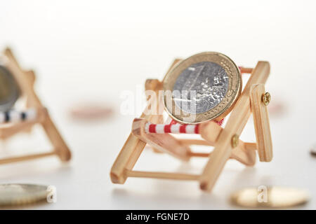 Pension concept shot with euro coin money relaxing on miniature lounger - Stock Photo