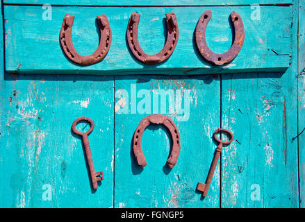 Two rusty iron antique keys and four horseshoes hanging on rustic wooden door - Stock Photo