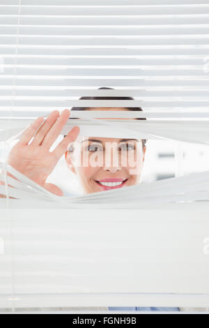 hand opening window shutters woman looking out through blinds stock photo