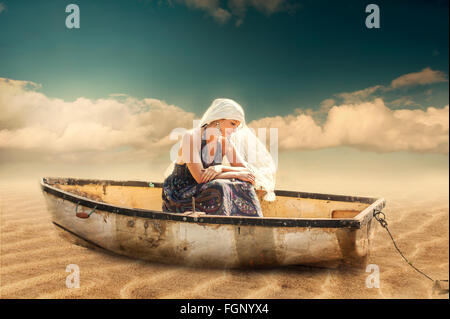 young beautiful exotic woman sitting in the boat on beach - Stock Photo