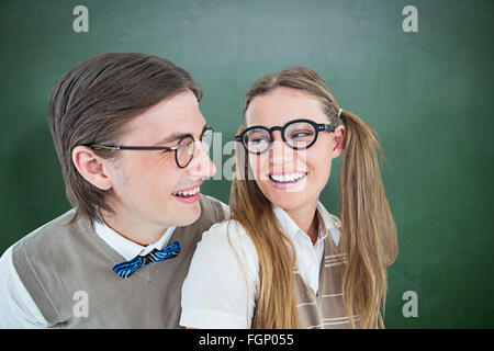 Composite image of geeky hipster couple smiling at each other - Stock Photo