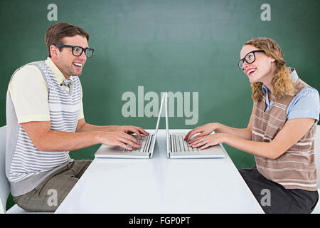 Composite image of geeky hipster couple using laptop - Stock Photo