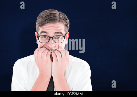 Composite image of geeky businessman looking nervously at camera - Stock Photo
