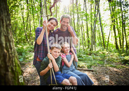 Portrait smiling family at rope swing in woods - Stock Photo