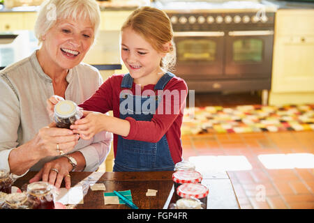Grandmother and granddaughter labeling canning jars in kitchen - Stock Photo