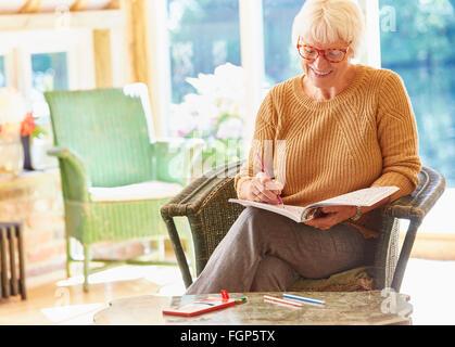 Senior woman coloring in coloring book - Stock Photo