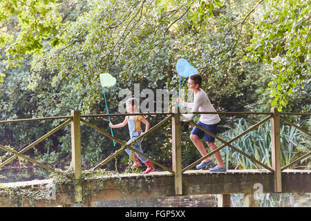 Brother and sister running with butterfly nets on footbridge in park - Stock Photo