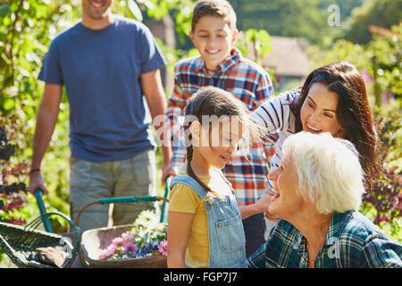 Multi-generation family bonding in sunny garden - Stock Photo