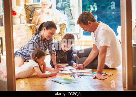 Family drawing and coloring on floor in living room - Stock Photo