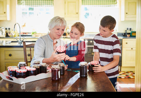 Grandmother canning jam with grandchildren in kitchen - Stock Photo