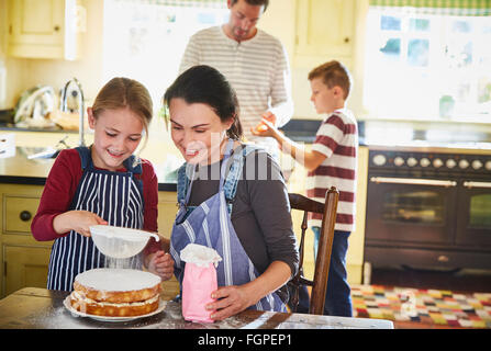 Family baking cake in kitchen - Stock Photo