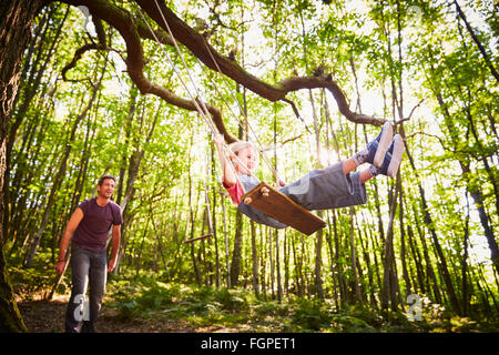 Father pushing daughter on rope swing in forest - Stock Photo