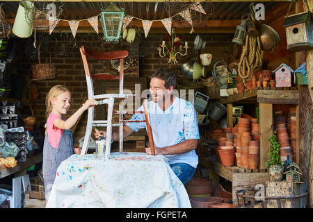 Father and daughter painting chair in workshop - Stock Photo