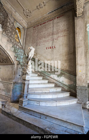 Ornate marble staircase with statue and words on wall with Fidel in apartment building at Havana, Cuba, West Indies, - Stock Photo