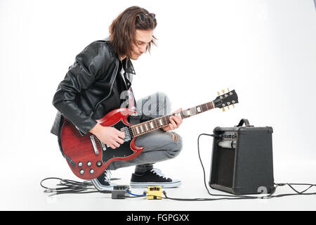 Focused handsome young guitarist playing electric guitar with amplifier over white background - Stock Photo