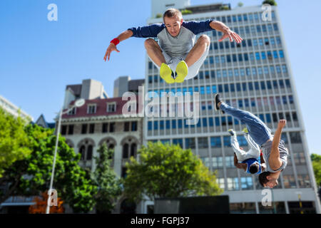 Happy friends doing parkour in the city - Stock Photo