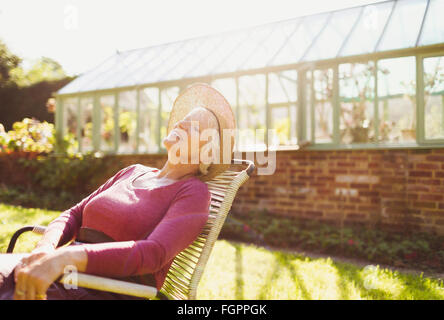 Carefree senior woman relaxing outside sunny greenhouse - Stock Photo