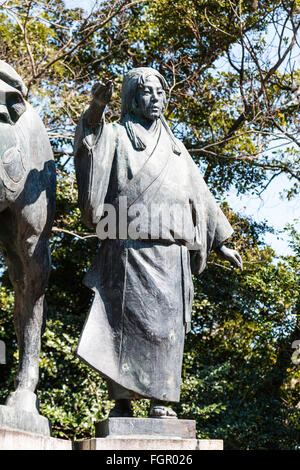 Japan, Kochi castle. Taka-jo. Statue of Yamauchi Chiyo. Woman dressed in traditional Japanese happi coat, with tree - Stock Photo