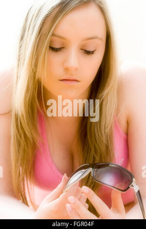 Caucasian blonde teenage girl with long blonde hair, facing, holding sunglasses, eyes cast down. Low cut pink t - Stock Photo