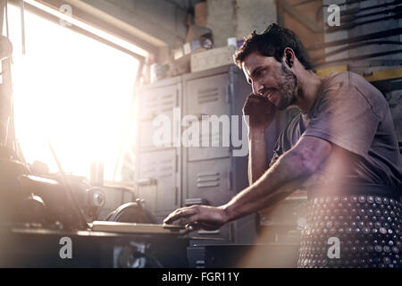 Blacksmith talking on cell phone in forge - Stock Photo