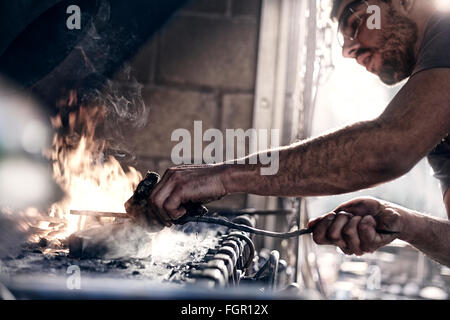 Blacksmith working over fire in forge - Stock Photo