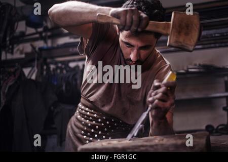 Blacksmith chiseling wood in forge - Stock Photo