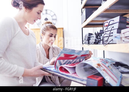 Interior designers browsing fabric swatches in office - Stock Photo