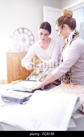 Interior designers photographing fabric swatches in office - Stock Photo