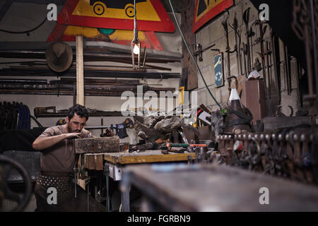 Blacksmith working in forge - Stock Photo