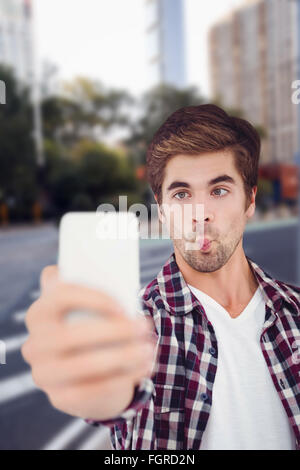 Composite image of man making face while taking selfie - Stock Photo