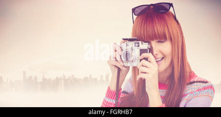 Composite image of smiling hipster woman taking pictures with a retro camera - Stock Photo