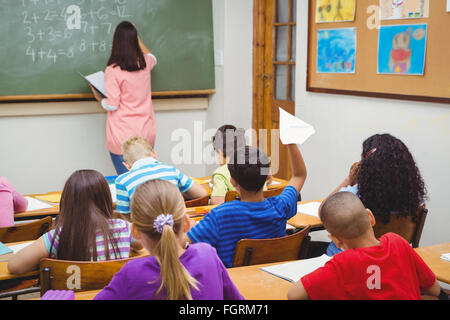 Student about to throw a paper airplane - Stock Photo