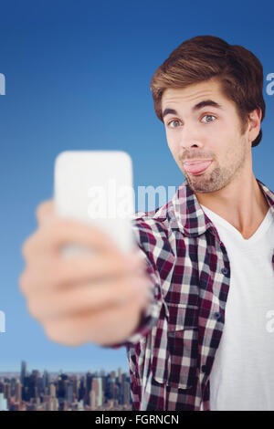 Composite image of hipster making face while taking selfie - Stock Photo