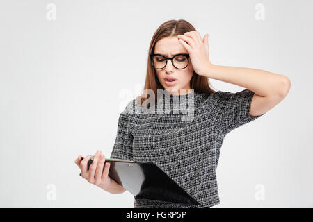 Stressed attractive young woman in glassed with clipboard having a headache over white background - Stock Photo