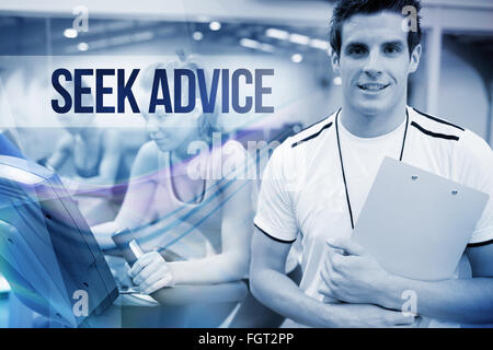 Seek advice against spinning class instructor holding clipboard - Stock Photo