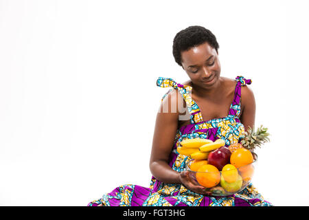 Pretty happy african american young woman in bright sundress sitting and looking at fresh exotic fruits over white - Stock Photo