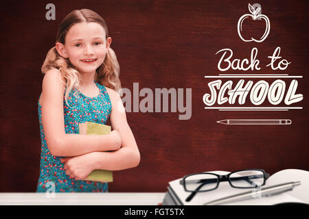 Composite image of girl holding book in library - Stock Photo