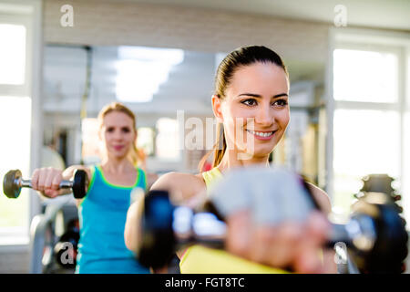 Two fit women in gym working out with weights - Stock Photo